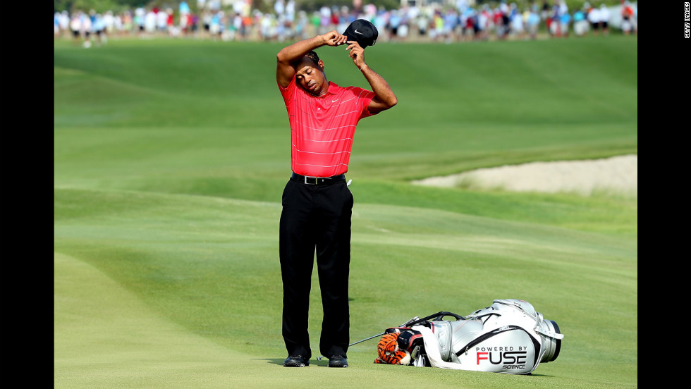 Woods, who finished the third round with a 74, wipes his brow between holes.
