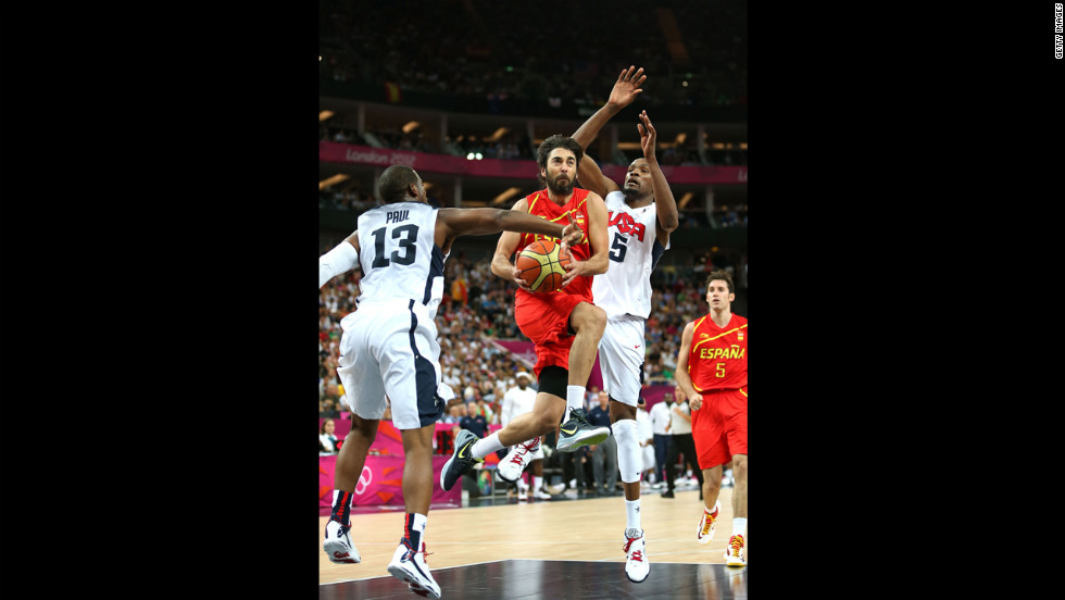 Juan-Carlos Navarro Spain drives to the goal past Kevin Durant and Chris Paul of the United States.