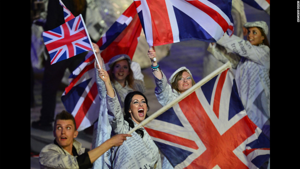 Artists wave Union Jack flags as they perform during the closing ceremony.