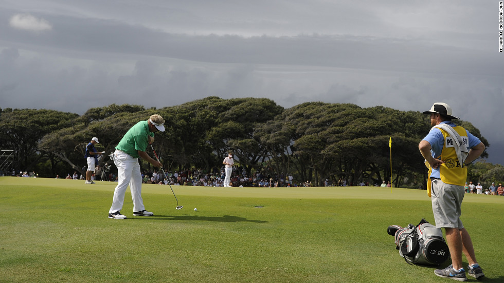 Carl Pettersson of Sweden tries a putt from the edge of the green as storm clouds move in.