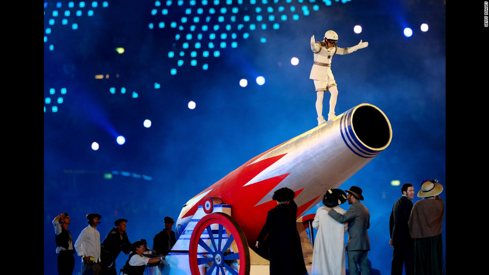 A performer stands on top of a giant cannon.