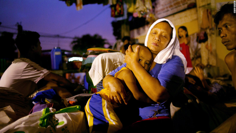 Lornitas Calub hugs her grandson at a crowded evacuation shelter in Manila on Monday.