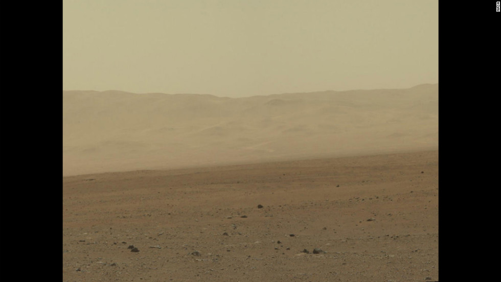 In this portion of the larger mosaic from the previous frame, the crater wall can be seen north of the landing site, or behind the rover. NASA says water erosion is believed to have created a network of valleys, which enter Gale Crater from the outside here.