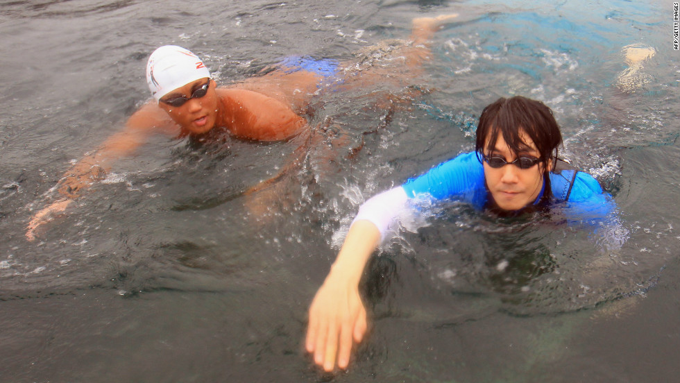 South Korean singer Kim Jang-Hoon (R) swims in the sea off Uljin, 225 kms southeast of Seoul, on August 13, 2012. He's among more than 40 swimmers who are part of a politically-charged relay team swimming from South Korea to the contested islands of Dokdo, or Takeshima as they're known in Japan.