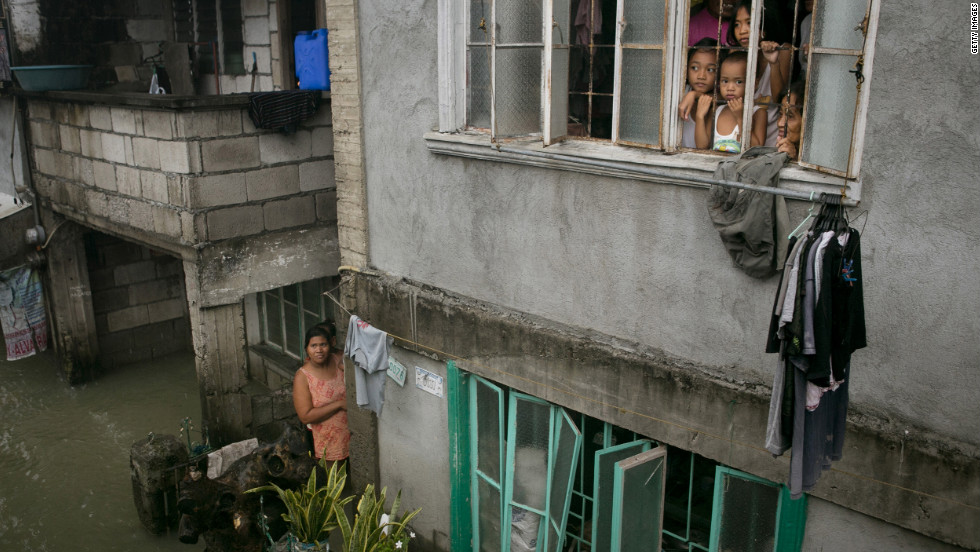 Children look out from their home Tuesday as more rain falls in the flooded coastal region in Bulacan.