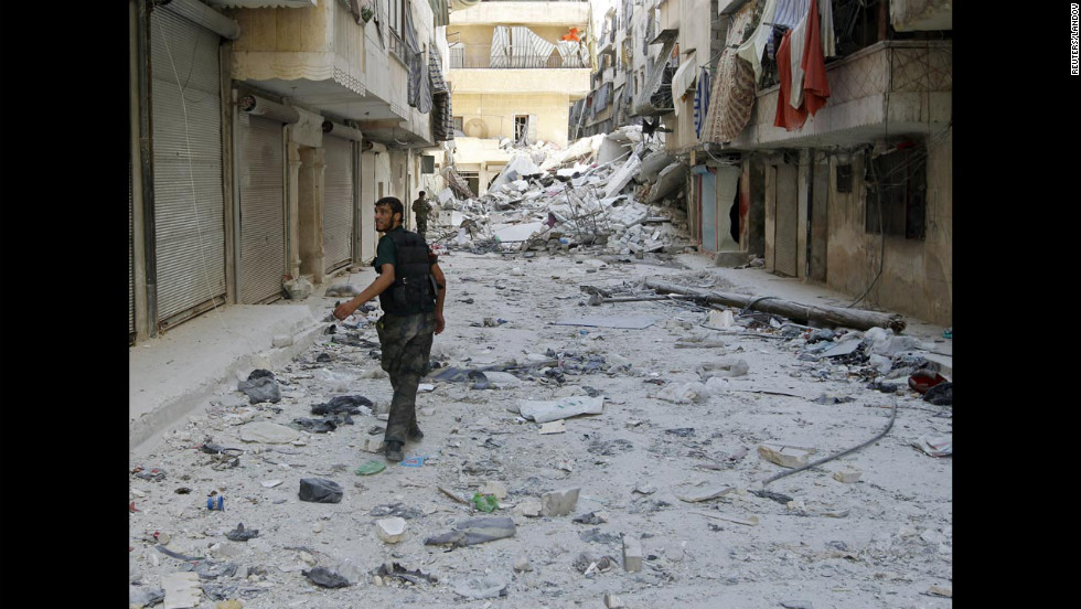 Free Syrian Army fighters walk down a debris-covered street Monday in central Aleppo's Salaheddine neighborhood.