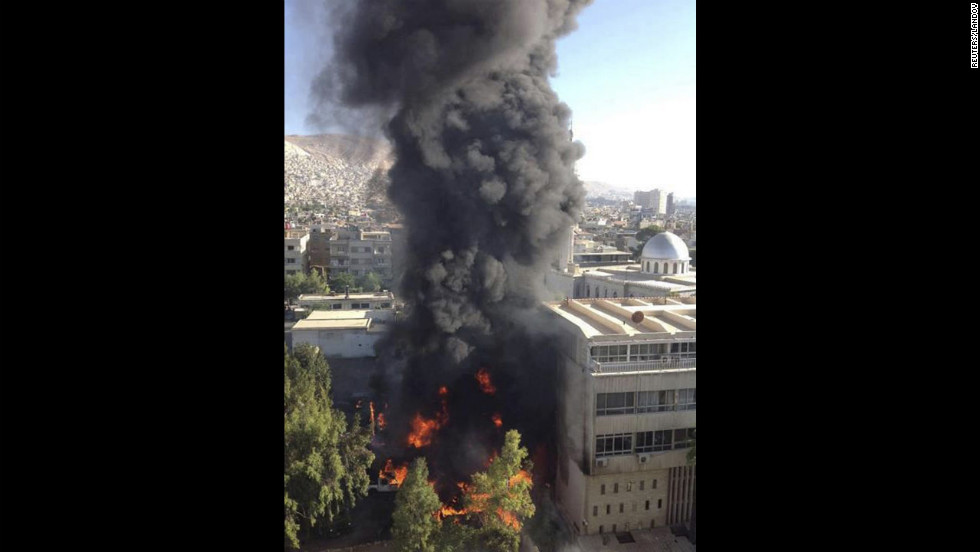 Black smoke billows into the air after a bomb exploded at a military site car park near a hotel used by United Nations monitors in Damascus. The explosion Wedesday wounded three people, Syrian state television said.