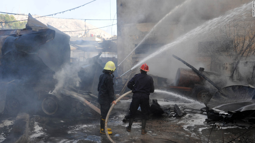 Firefighters work at the scene of a bomb explosion in central Damascus. The bomb was planted under a diesel tanker.