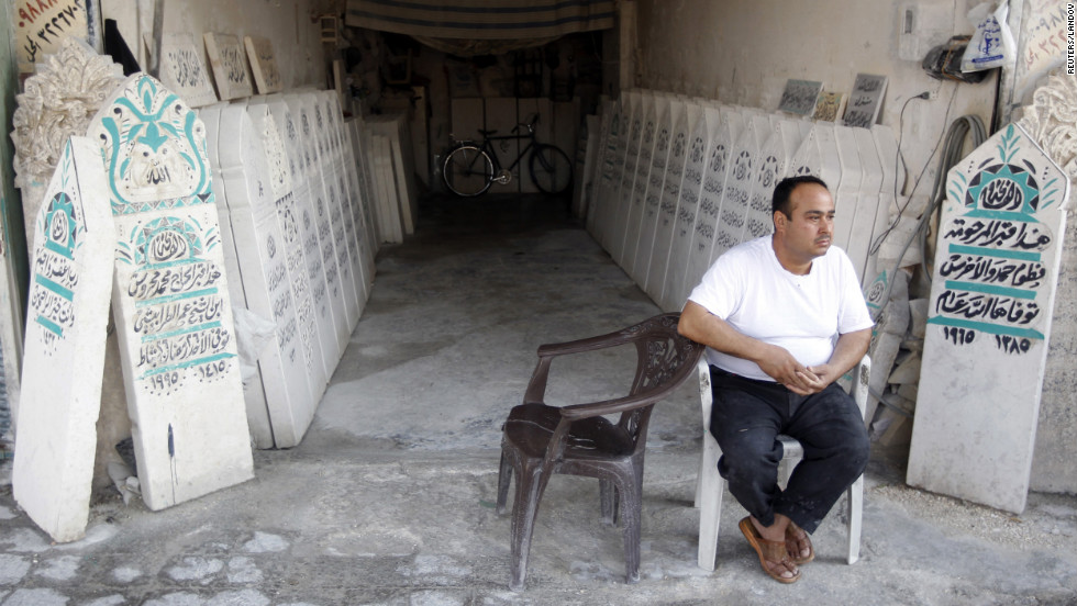 A man sits in front of tombstone workshop in Aleppo.