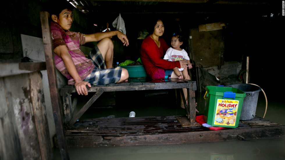 Leo Sampilay, his wife, Anna, and 1-year-old daughter, Kim, sit in their  home in a flooded province in Bulacan, Philippines.