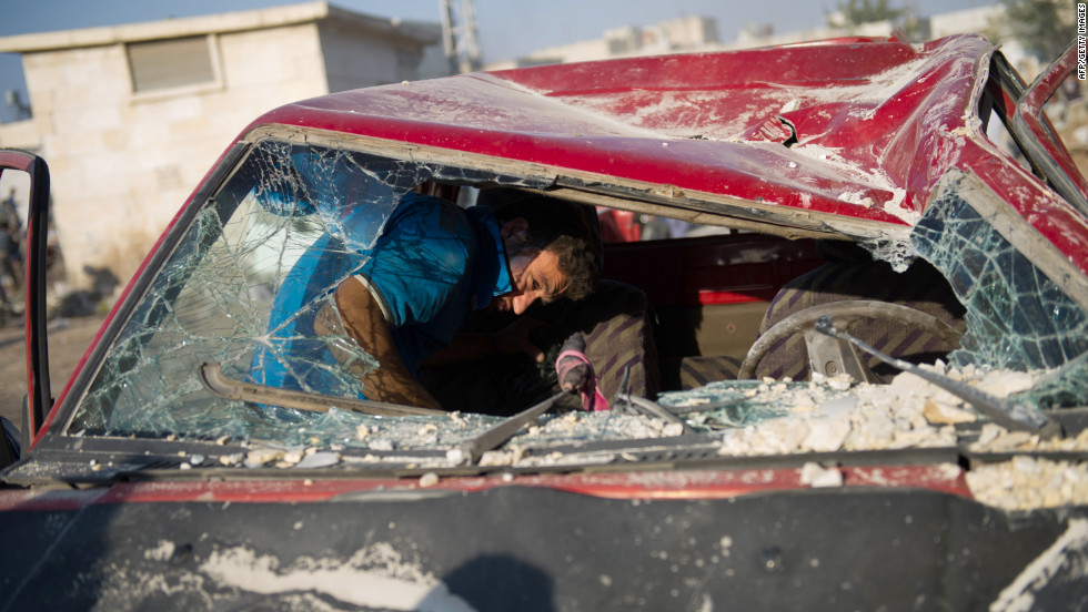 A man removes his belongings from his destroyed car at the airstrike site.