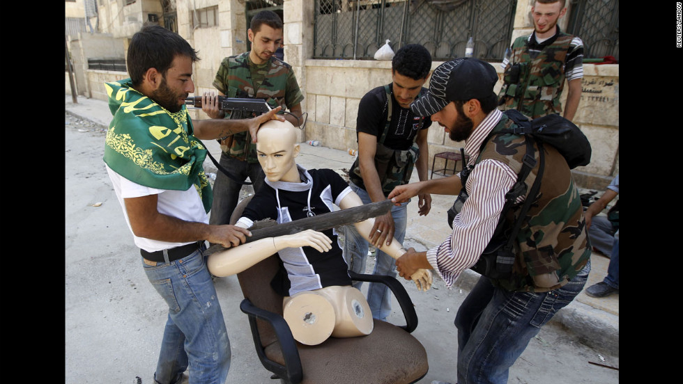 Free Syrian Army fighters dress a mannequin to look like a fighter to draw gunfire away from them Friday in Aleppo.