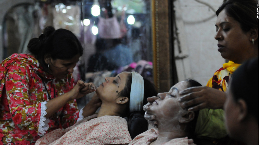 Pakistani beauticians attend to their customers ahead of the Muslim festivities of Eid al-Fitr, in Karachi.