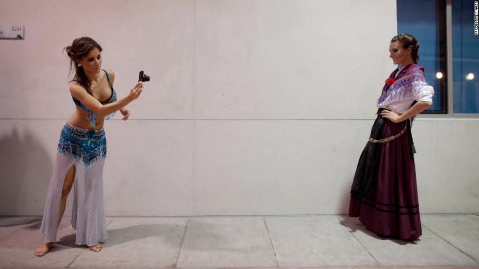 Miss Hungary Tamara Cserhati, left, and Miss Slovenia Nives Oresnik take photos prior to a rehearsal.