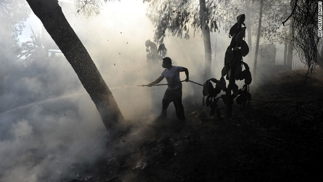 A volunteer firefighter helps extinguish a blaze Saturday near the village of Kehries in the Peloponnese region of southern Greece.