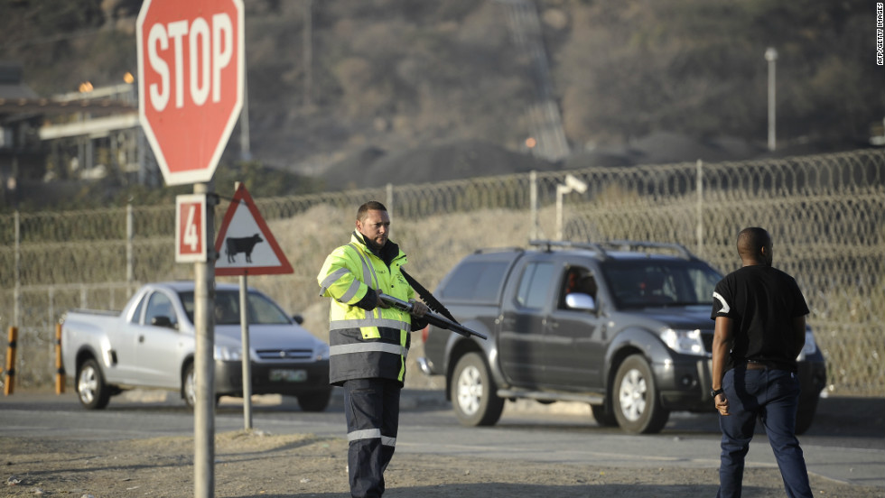 A private security guard mans the entrance to the Marikana platinum mine on August 21 where five days earlier police opened fire on striking workers. The violence left 34 dead.
