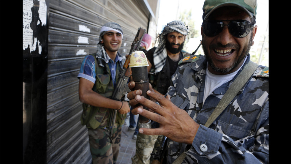 A Syrian rebel fighter holds a handmade bomb in the Saif al-Dawla district in the center of Aleppo on August 22.
