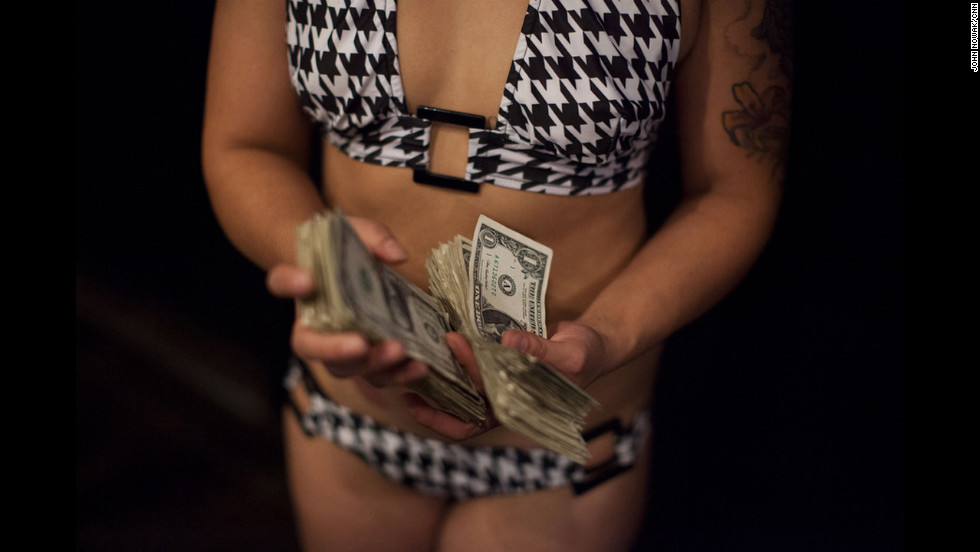 Eziil, who dances at 2001 Odyssey, holds two stacks of dollar bills.