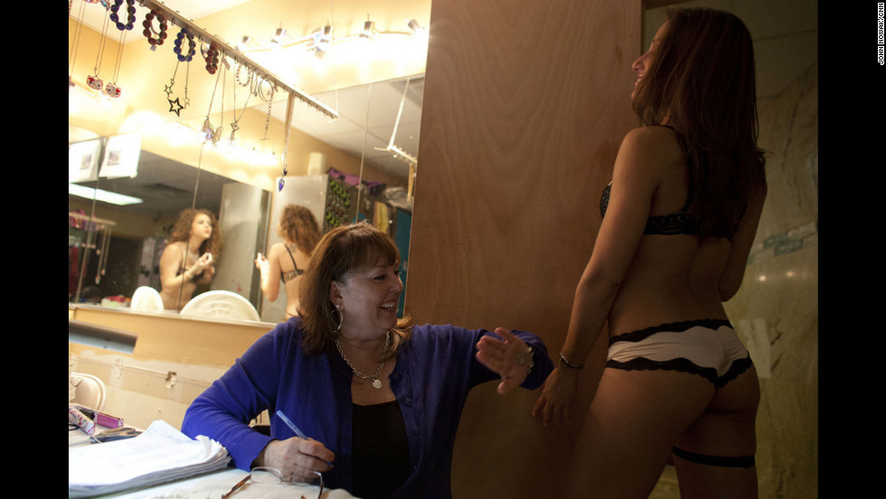 "House mom Wendy Karafas playfully spanks Sasha backstage at Thee DollHouse. Karafas organizes the schedules and inspects dancers before they go out onstage. They refer to her as ""mom.""   <br />"