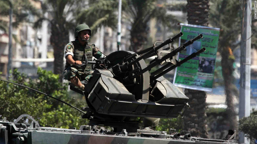 A Lebanese soldier mans an anti-aircraft heavy machine gun mounted on an armored personal carrier Wednesday in Tripoli. The Syrian civil war has aggravated decades-old quarrels in two of the city's neighborhoods.