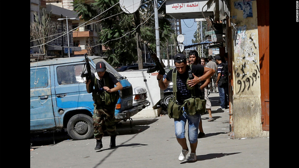 Supporters of the Syrian uprising run down a street in Tripoli's Bab al Tabaneh neighborhood Wednesday. Sniper fire broke out in two neighborhoods of the Lebanese seaport: one dominated by Alawite Muslims, the other by Sunni Muslims.