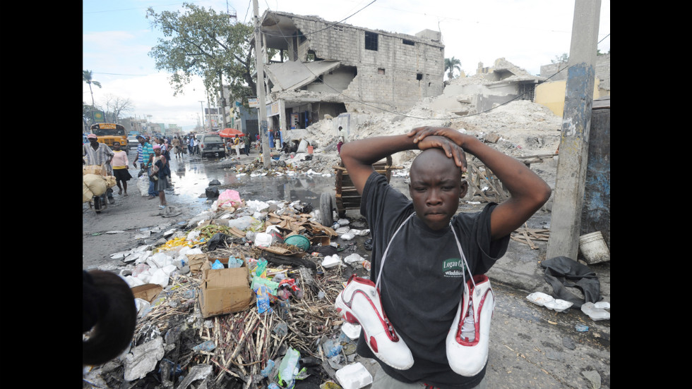 A Haitian man sells used shoes in Port-au-Prince amid earthquake damage on January 9.