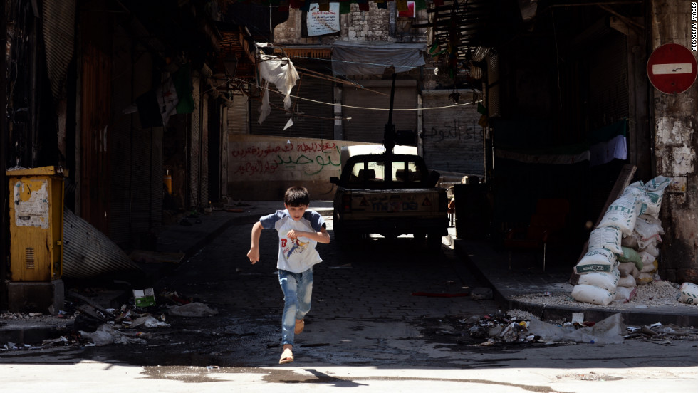 A young boy runs across the street during clashes between Free Syrian Army fighters and forces loyal to al-Assad.