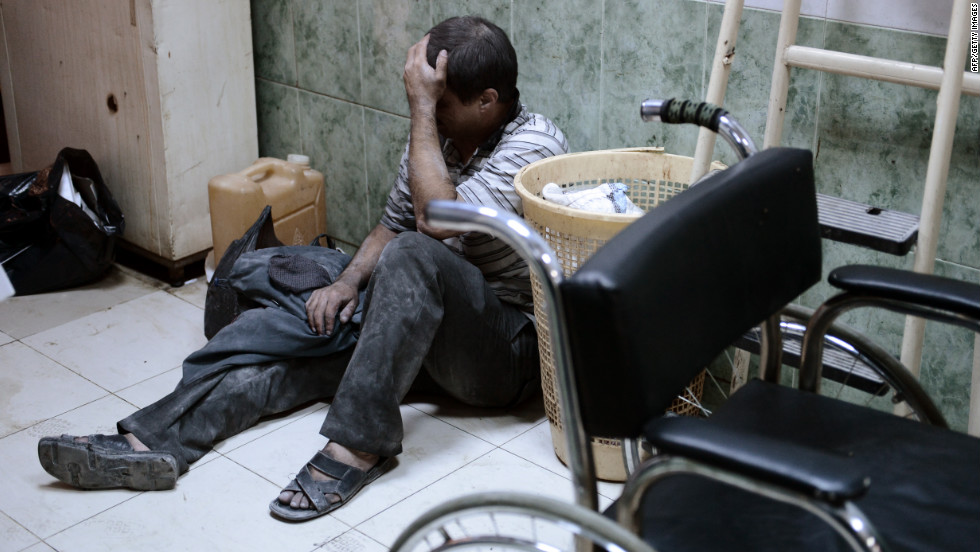 A Syrian man reacts outside an operation room as doctors treat his grandchildren after an airstrike by regime forces.