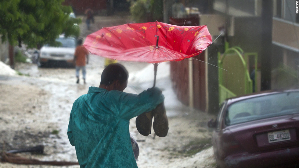 A man tries to stay dry in Port au Prince, Haiti, after Tropical Storm Isaac hit in  August, 2012.