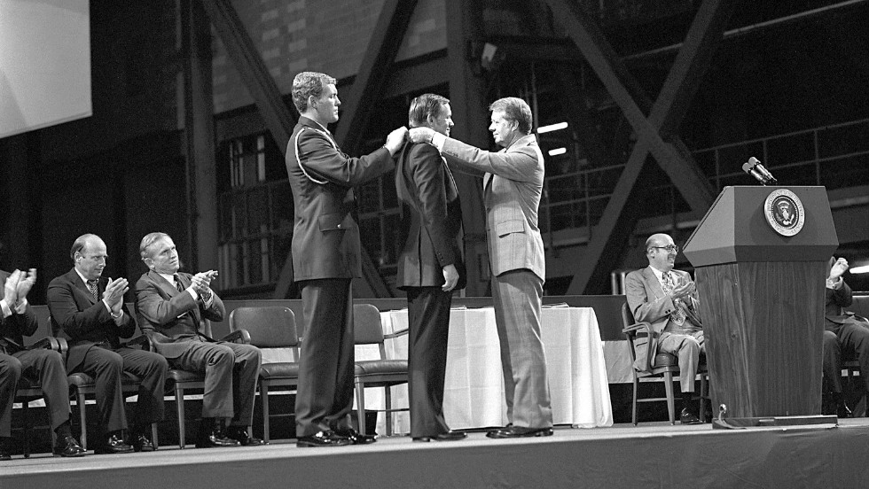 Armstrong receives the first Congressional Space Medal of Honor from President Jimmy Carter, right, assisted by Capt. Robert Peterson, on October 1, 1978. Armstrong, one of six astronauts to be presented the medal during ceremonies held in the Vehicle Assembly Building (VAB), was awarded for his performance during the Gemini 8 mission and the Apollo 11 mission.