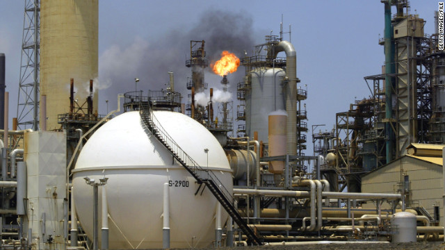 A controlled flame burns behind a storage tank in the oil refinery complex of Amuay-Cardon on April 4, 2003 in Paraguana, Venezuela.