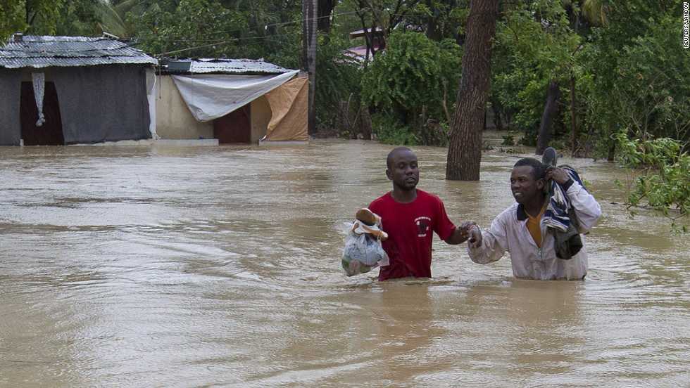 Residents of a low-lying area in Port-au-Prince flee their flooded homes with their possessions.