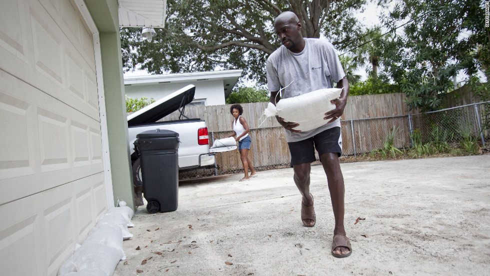 Earl, right, and Terri Harris place sandbags around their home to prepare for possible flooding.