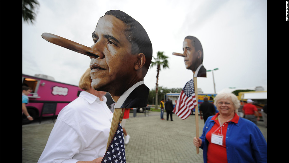 Activists hold signs mocking President Barack Obama at the Tea Party Unity Rally at The River at Tampa Bay Church.
