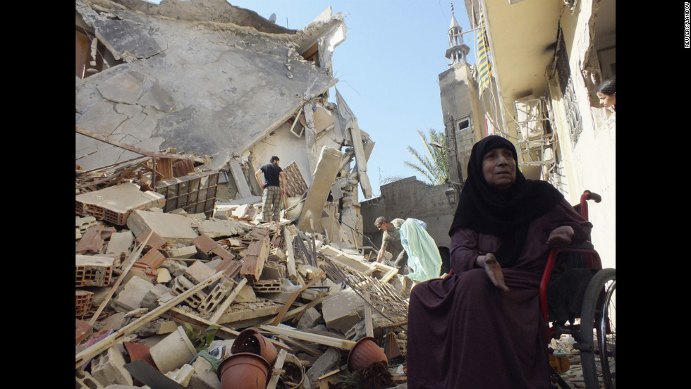 A woman sits in her wheelchair next to her house, damaged by an army air raid, near Homs on Sunday, August 26.