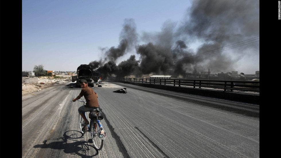 A boy rides a bicycle toward fuel trucks struck by missiles from fighter jets in the Bab al-Nayrab district of Aleppo, Syria, on Monday, August 27.