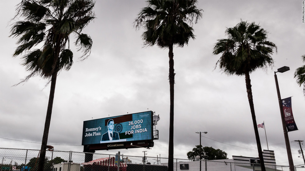 A billboard opposing Mitt Romney stands among palm trees Monday.