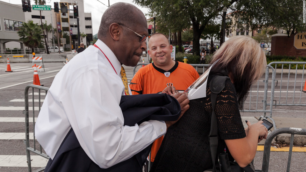 Former Republican presidential candidate Herman Cain, left, with support from his assistant, signs a photograph of himself for political fan Kieth Klickna.