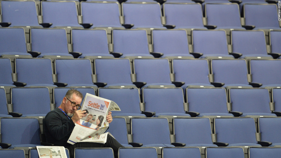 A man reads a newspaper in the empty seats of the Tampa Bay Times Forum.