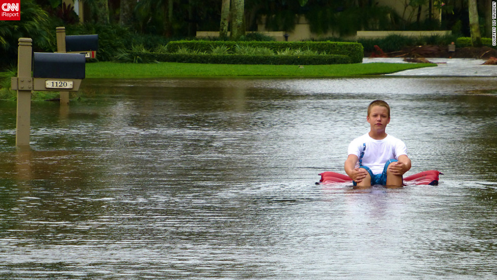 iReporter Liz Yavinsky snapped this picture of a boy floating down a flooded street in West Palm Beach, Florida, on Monday.