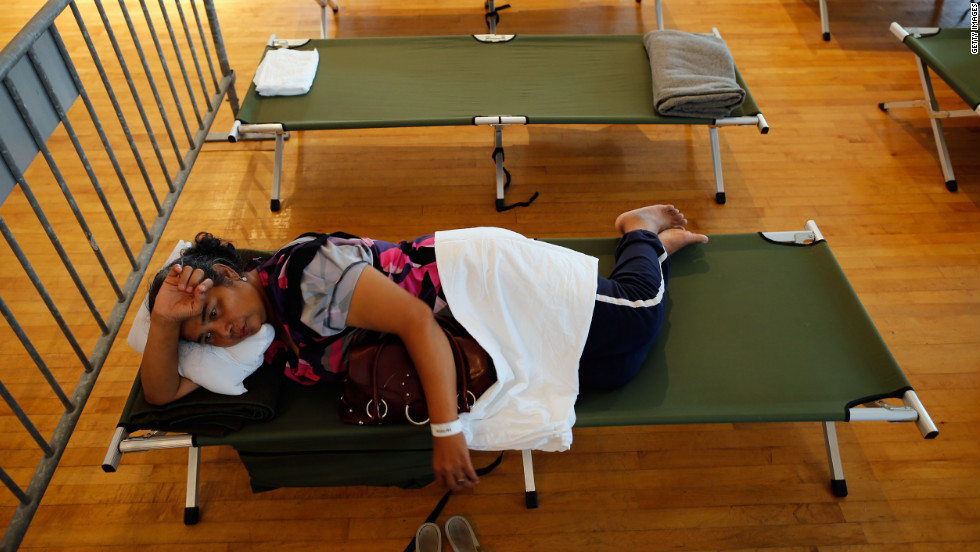 Aimo Ny rests on her cot in the hurricane shelter at the Belle Chasse Auditorium on Monday in Belle Chasse, Louisiana.