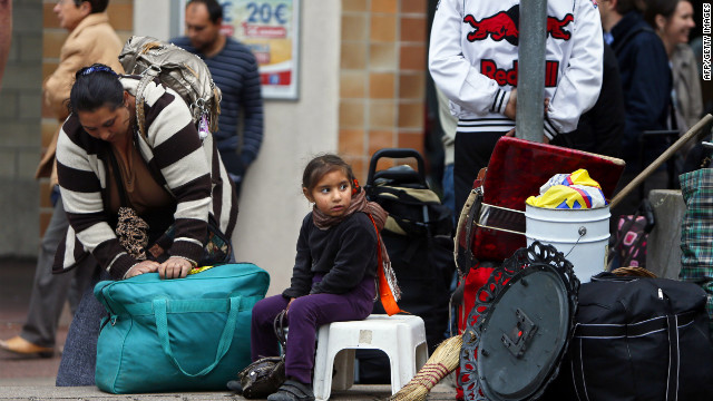 People from the Roma community wait outside their camp in Evry, near Paris,  August 27, 2012.