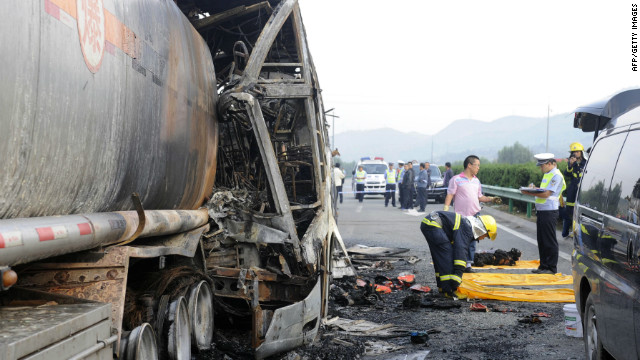 Police and rescuers remove bodies from a burnt out double-decker sleeper bus on Sunday.