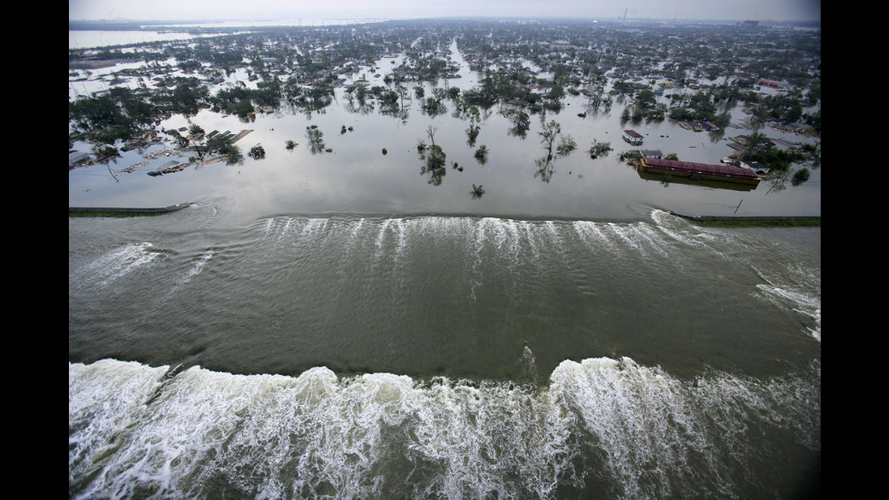 Water spills over a levee along the Inner Harbor Navigational Canal in the aftermath of Hurricane Katrina on August 30, 2005, in New Orleans. Katrina struck the Gulf Coast on August 29, 2005. After levees and flood walls protecting New Orleans failed, much of the city was underwater.