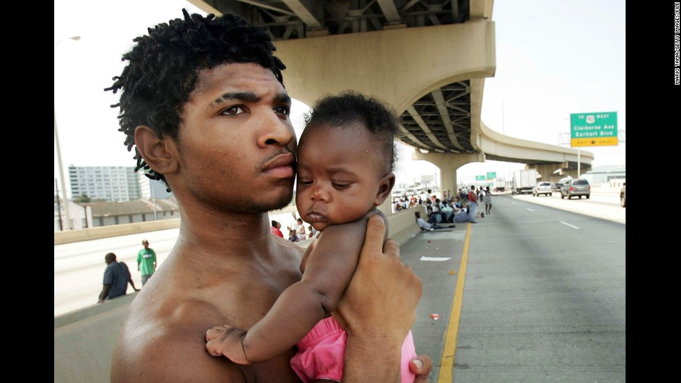 Daryl Thompson and his daughter Dejanae, 3 months old, wait with other displaced residents on a highway to catch a ride out of New Orleans on August 31, 2005. Thousands were looking for a place to go after leaving the Superdome shelter.