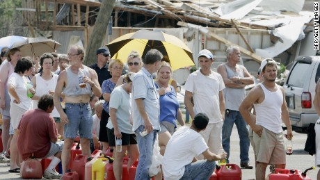 SAUCIER, UNITED STATES:  Saucier, Mississippi, residents line up to get gas 31 August, 2005, which is limited to five gallons per person. The gas is being hand-pumped as electricity is cutoff after the passing of Hurricane Katrina. Saucier is 20 miles (32kms) north of Gulfport.  AFP PHOTO/Robert SULLIVAN  (Photo credit should read ROBERT SULLIVAN/AFP/Getty Images)