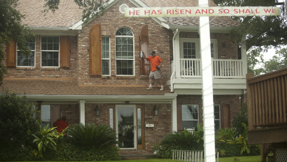 Jason Preston closes shutters on a home in Gulfport, Mississippi, as Hurricane Isaac approaches.