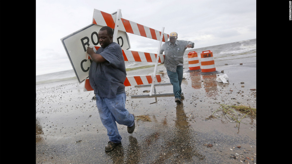 Employees of the Orleans Levee District remove signs from Lake Shore Drive near the shore of Lake Pontchartrain.