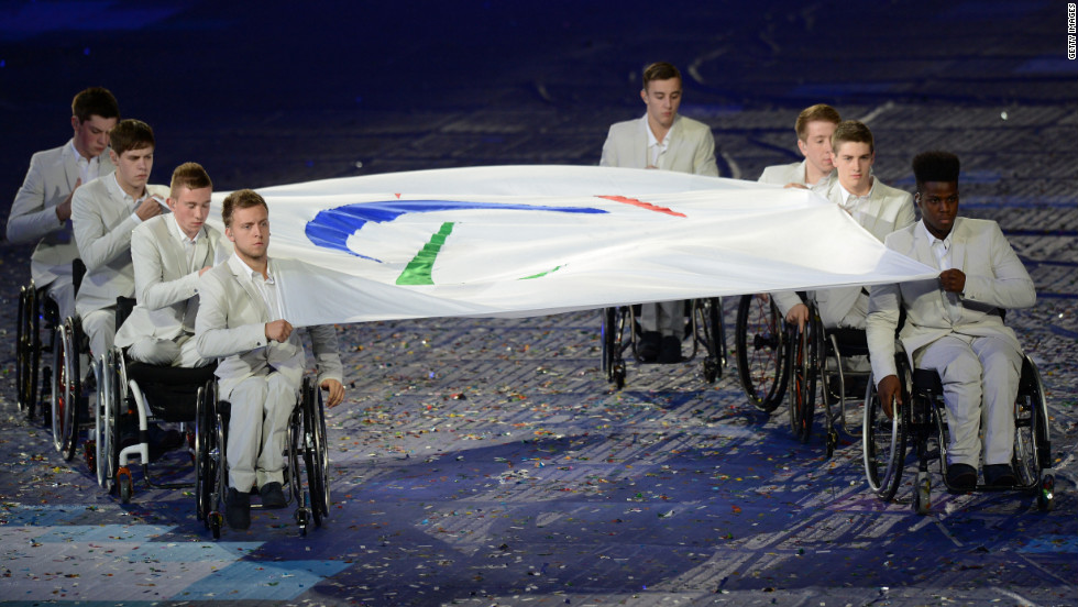 The Paralympic flag is carried by members of the Great Britain wheelchair basketball team.