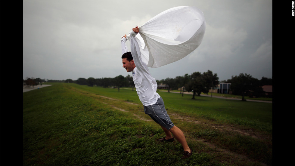 Matthew Pettus holds a sheet open in the wind on the levee near  Lake Pontchartrain.